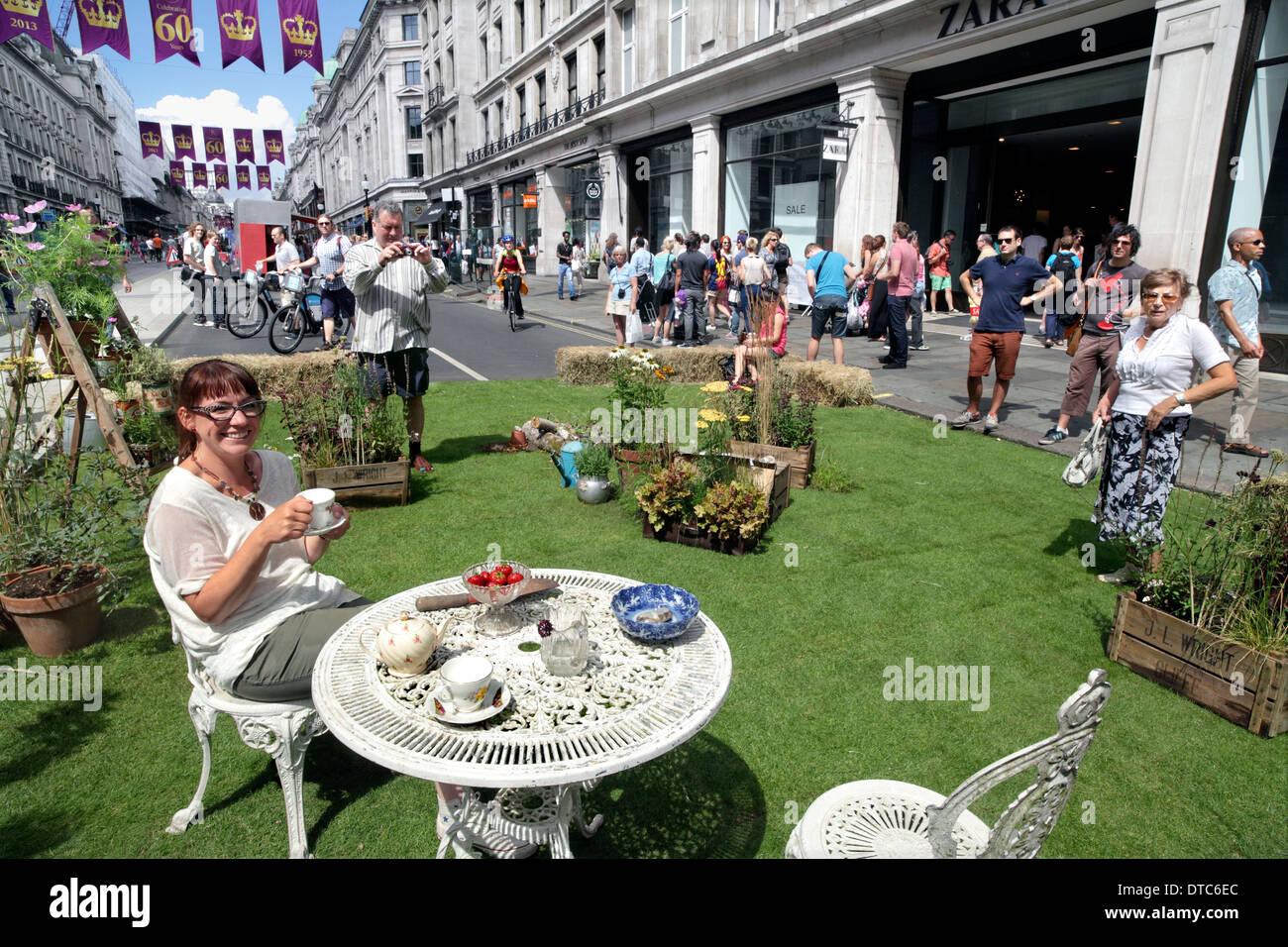 Rachel Parker Soden enjoys a cup of tea in her pop-up garden in London's Regent Street on 28 July 2013. [Event described below] - Stock Image