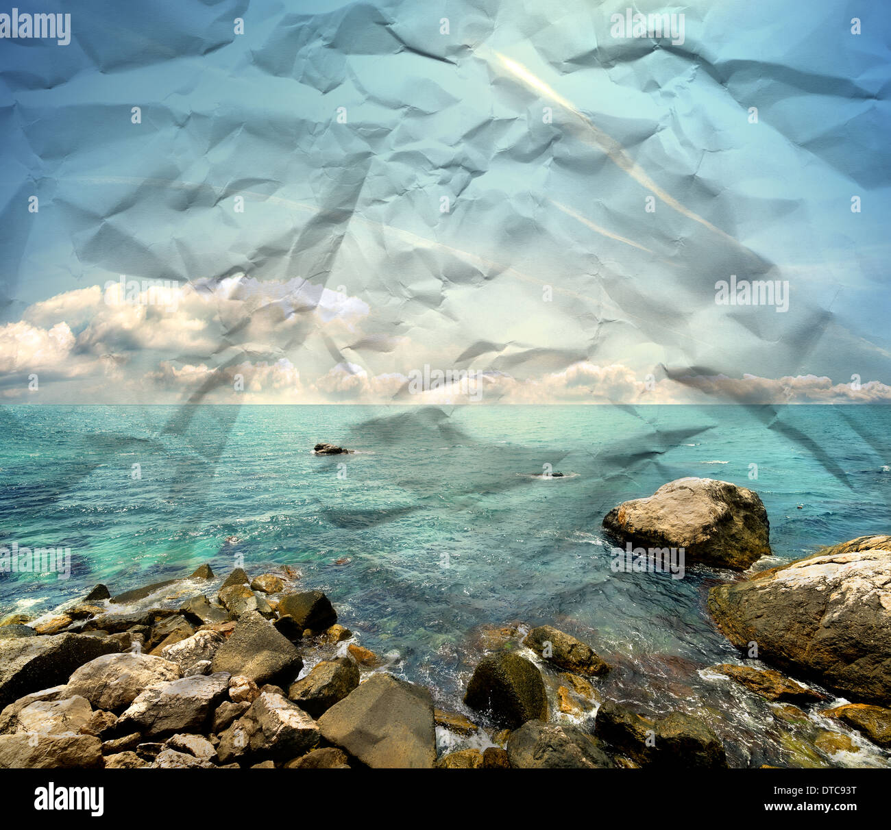 Stony beach, clear sea and blue cloudy sky on a paper texture - Stock Image