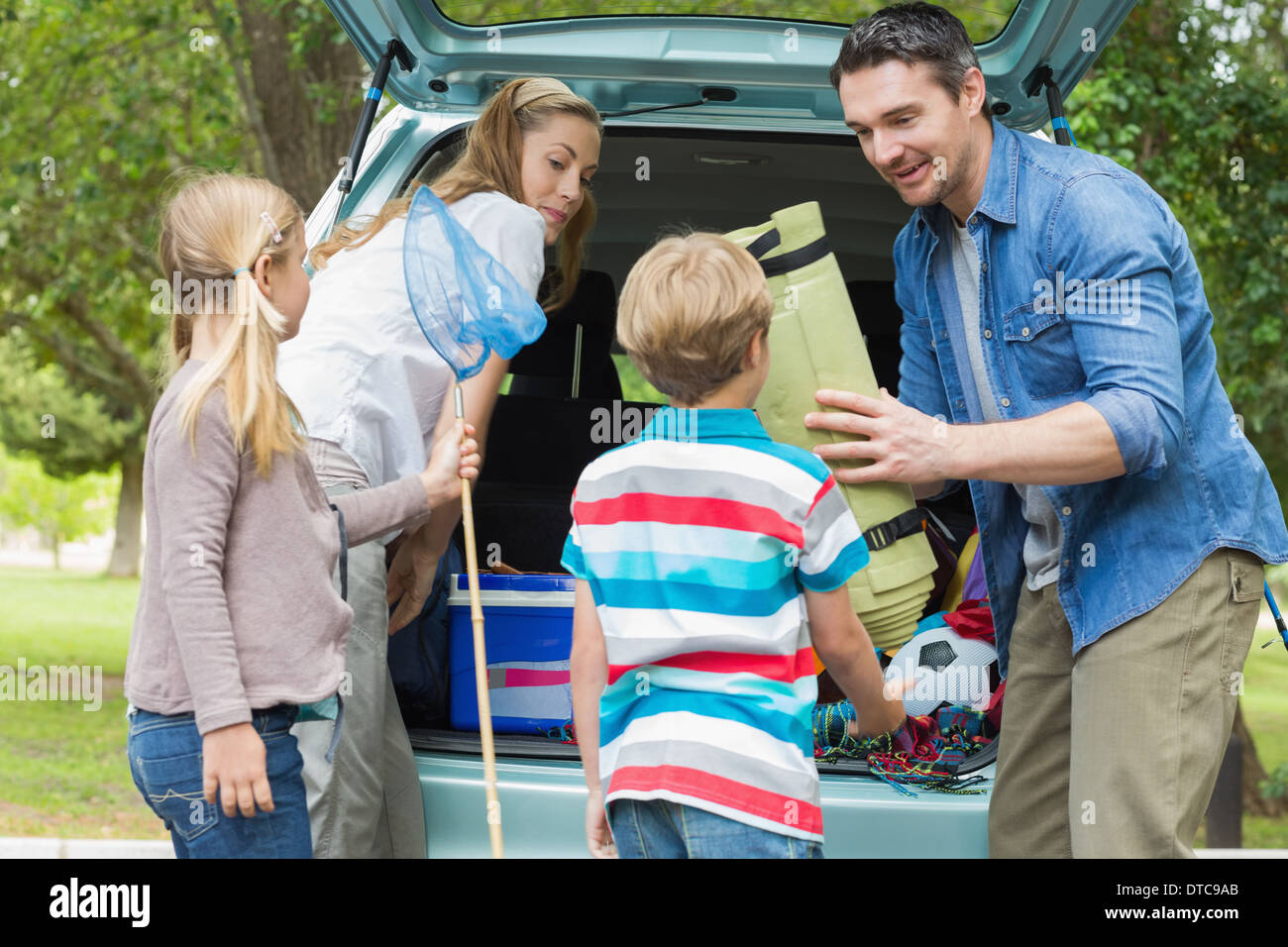 Family unloading car trunk while on picnic - Stock Image