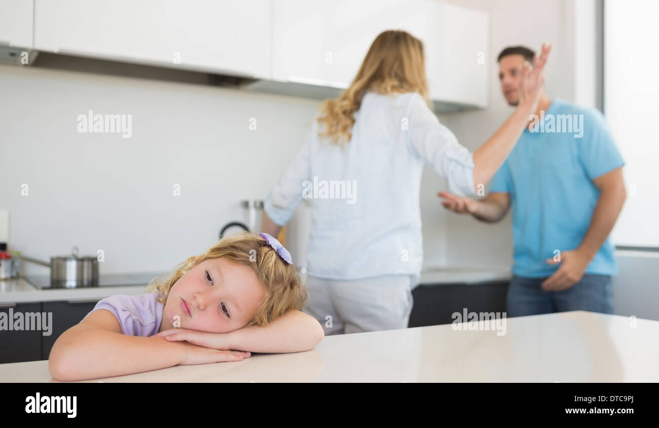 Bored girl leaning on table while parents arguing - Stock Image