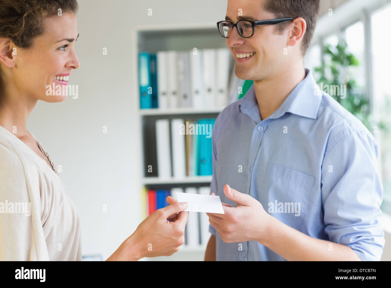 Smiling business people exchanging visiting card - Stock Image