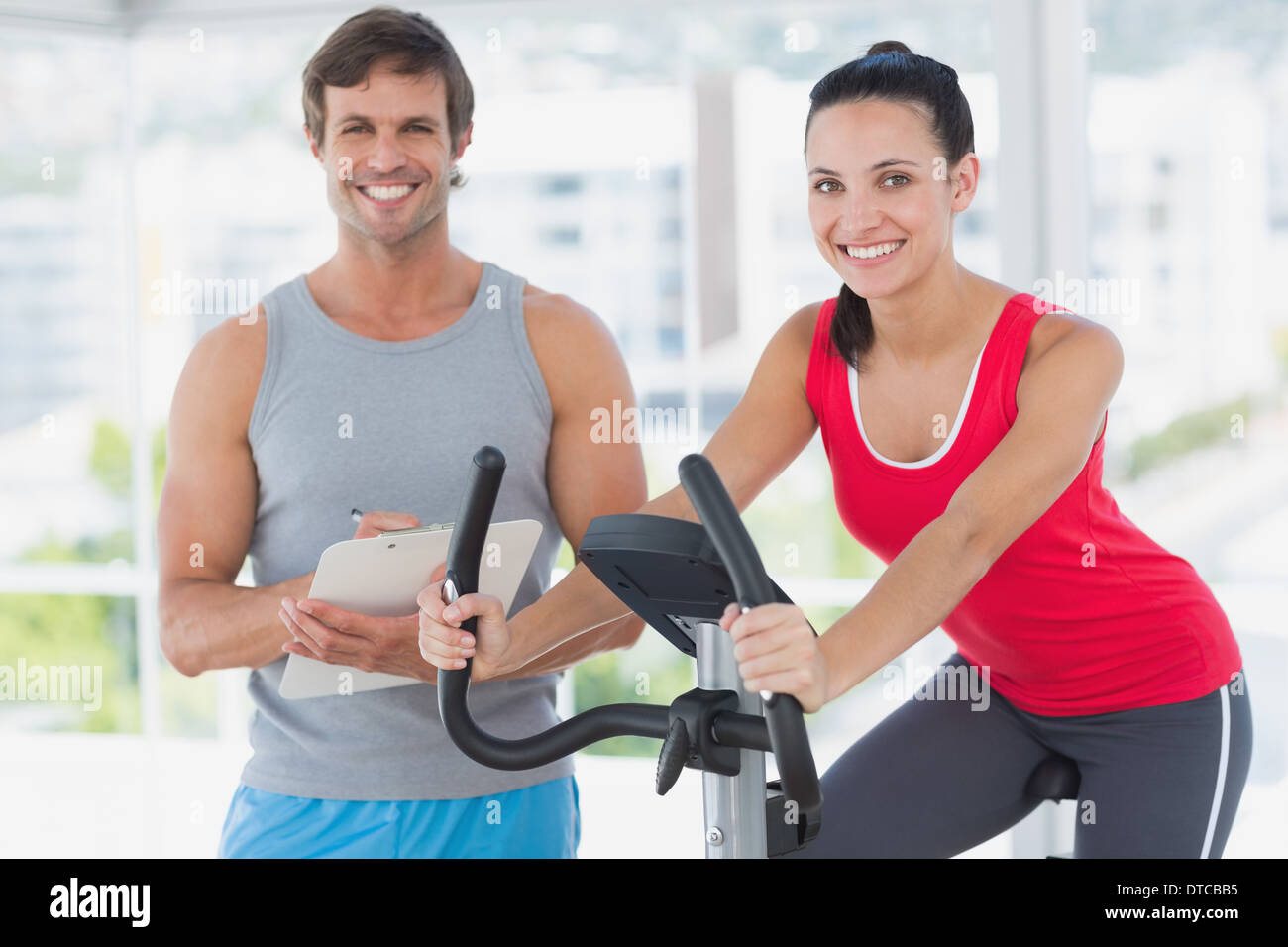 Woman with instructor working out at spinning class in bright gym - Stock Image
