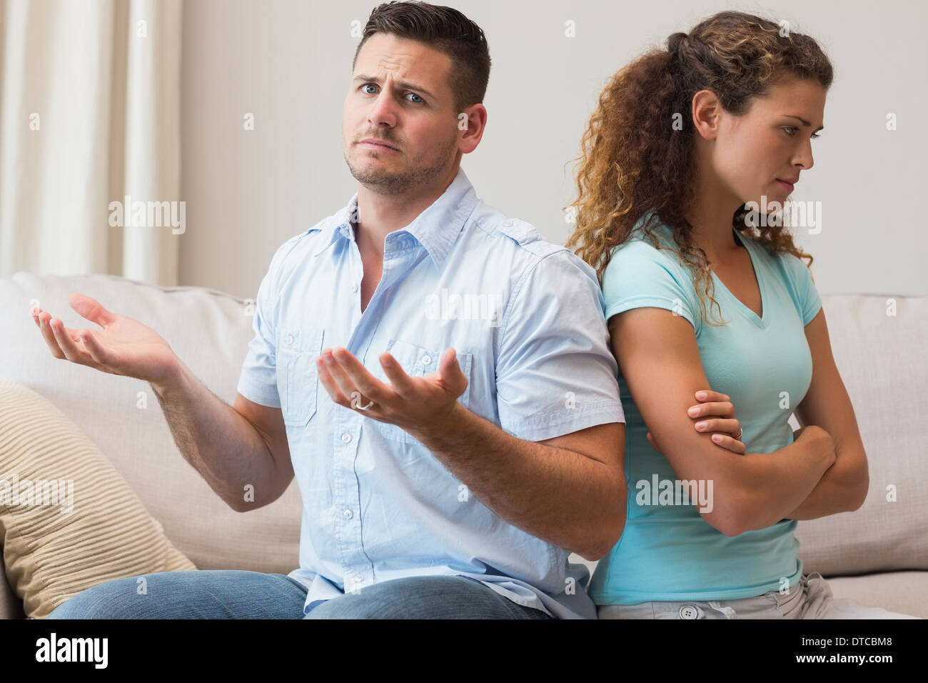 Man gesturing while arguing with woman - Stock Image