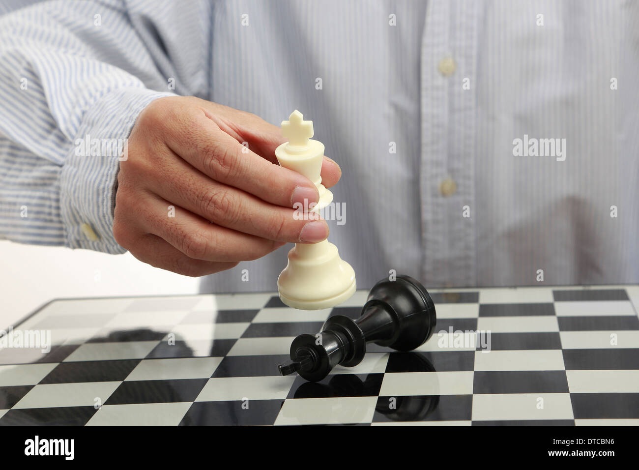 Male hand with a chess king on chessboard - Stock Image