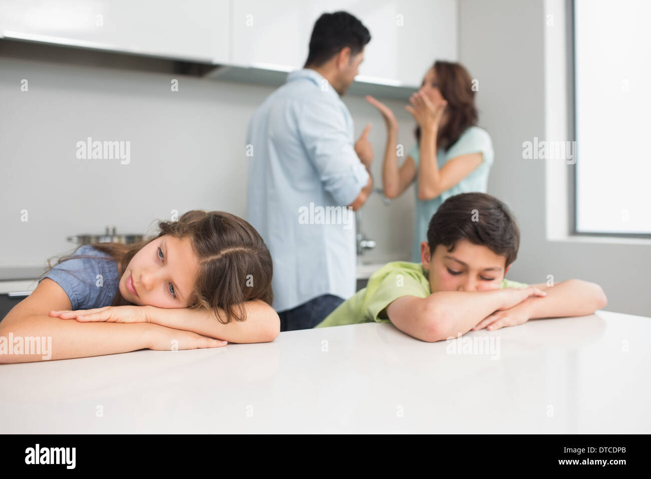 Sad young kids while parents quarreling in kitchen - Stock Image