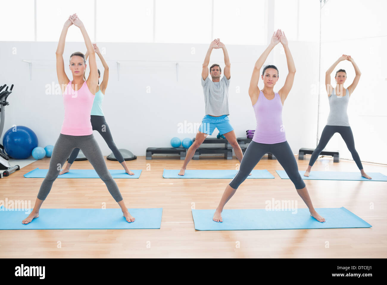 Class doing pilate exercises in fitness studio - Stock Image