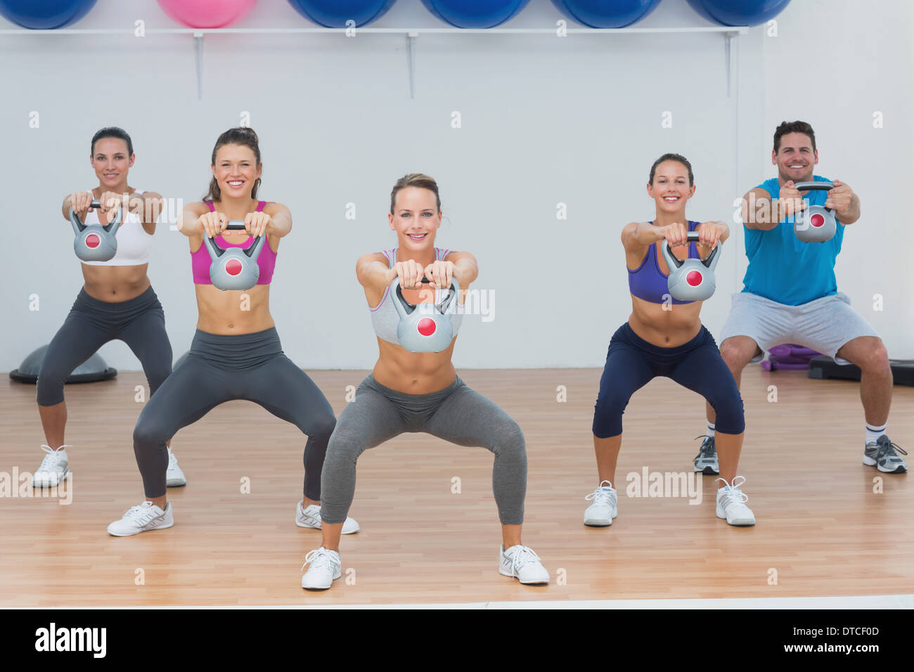 Fitness class exercising with kettlebells in gym - Stock Image