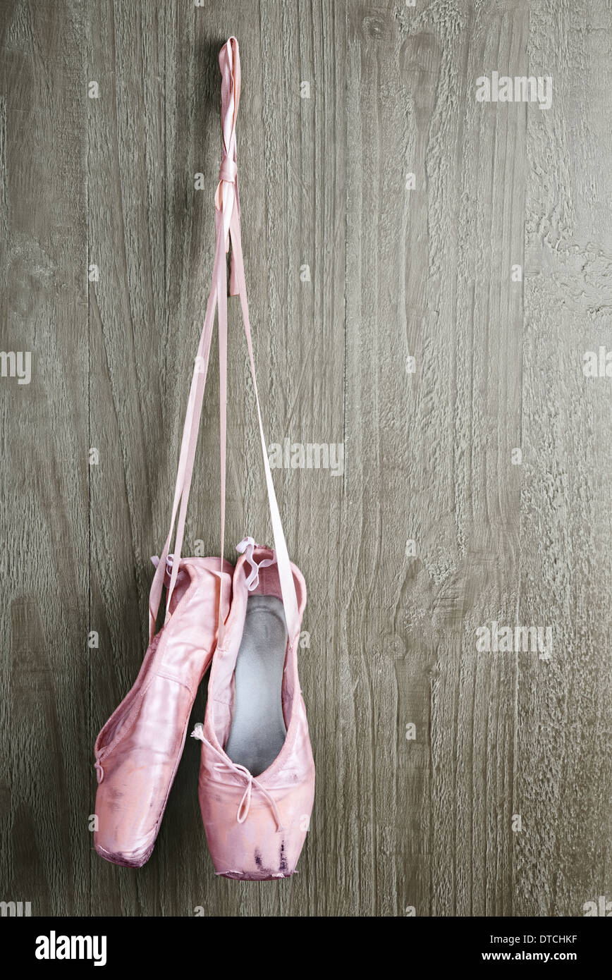 Old used pink ballet shoes hanging on wooden background - Stock Image