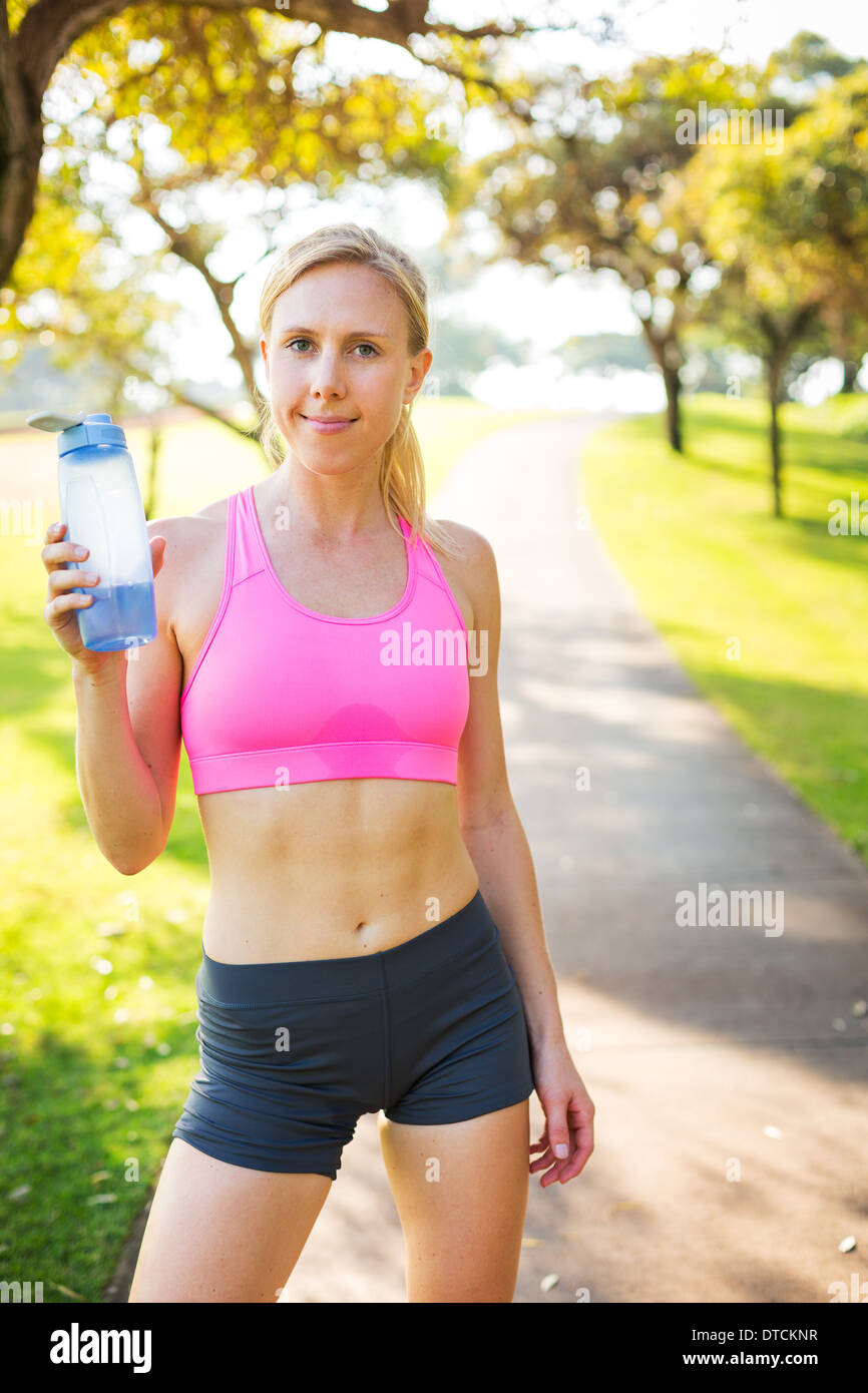 Athletic young woman drinking water and relaxing after early morning workout, Running in the park. - Stock Image
