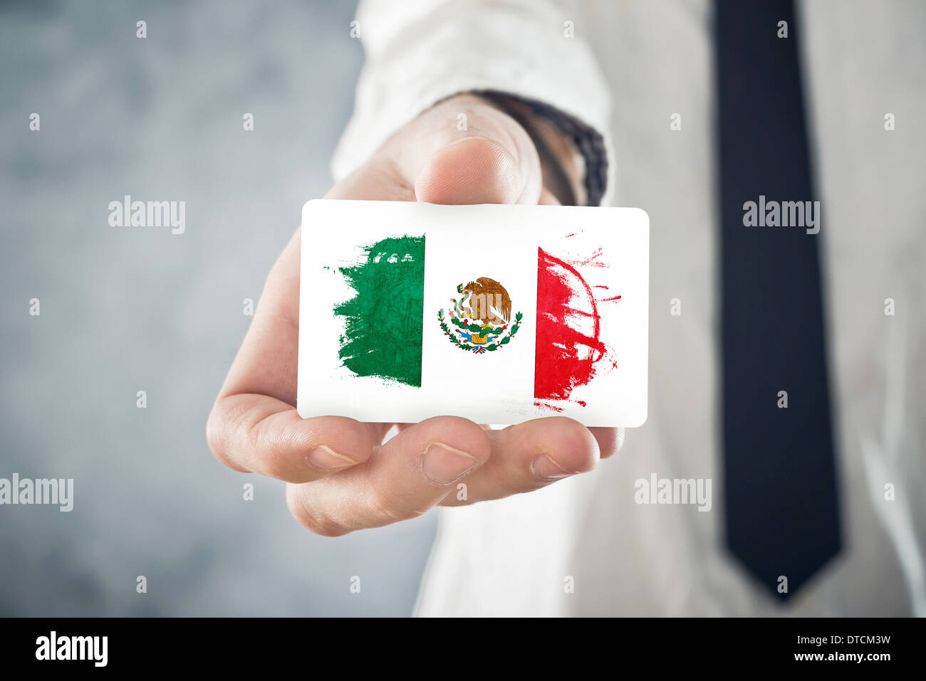 Mexican Businessman holding business card with Mexico Flag. International cooperation, investments, business opportunities - Stock Image