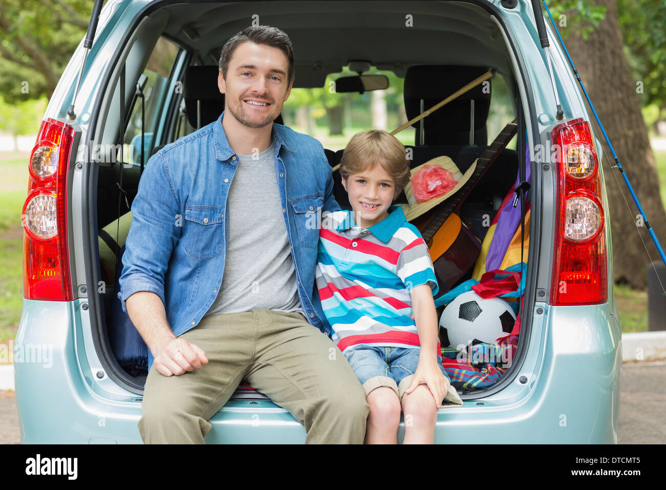 Happy father and son sitting in car trunk - Stock Image