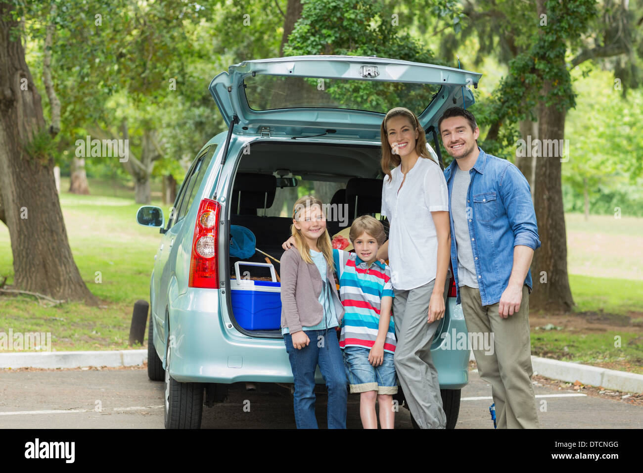 Family of four by car trunk while on picnic - Stock Image