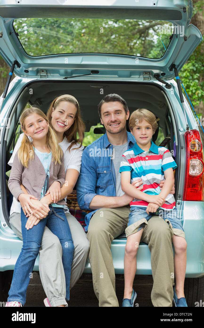 Happy family of four sitting in car trunk - Stock Image