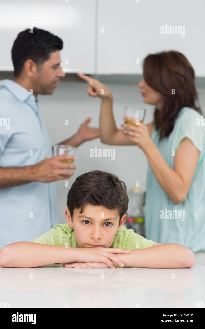 Portrait of a sad son while parents quarreling - Stock Image