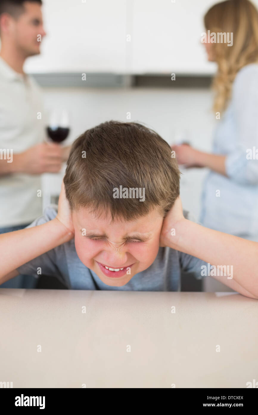 Furstrated boy covering ears while parents arguing - Stock Image
