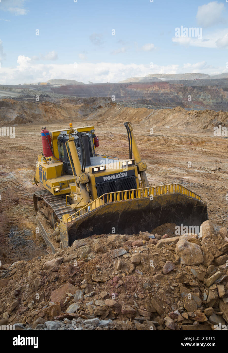 A massive yellow komatsu bulldozer pushes waste rock and soil in a large open cast copper and golf mine in Zambia, Africa. - Stock Image