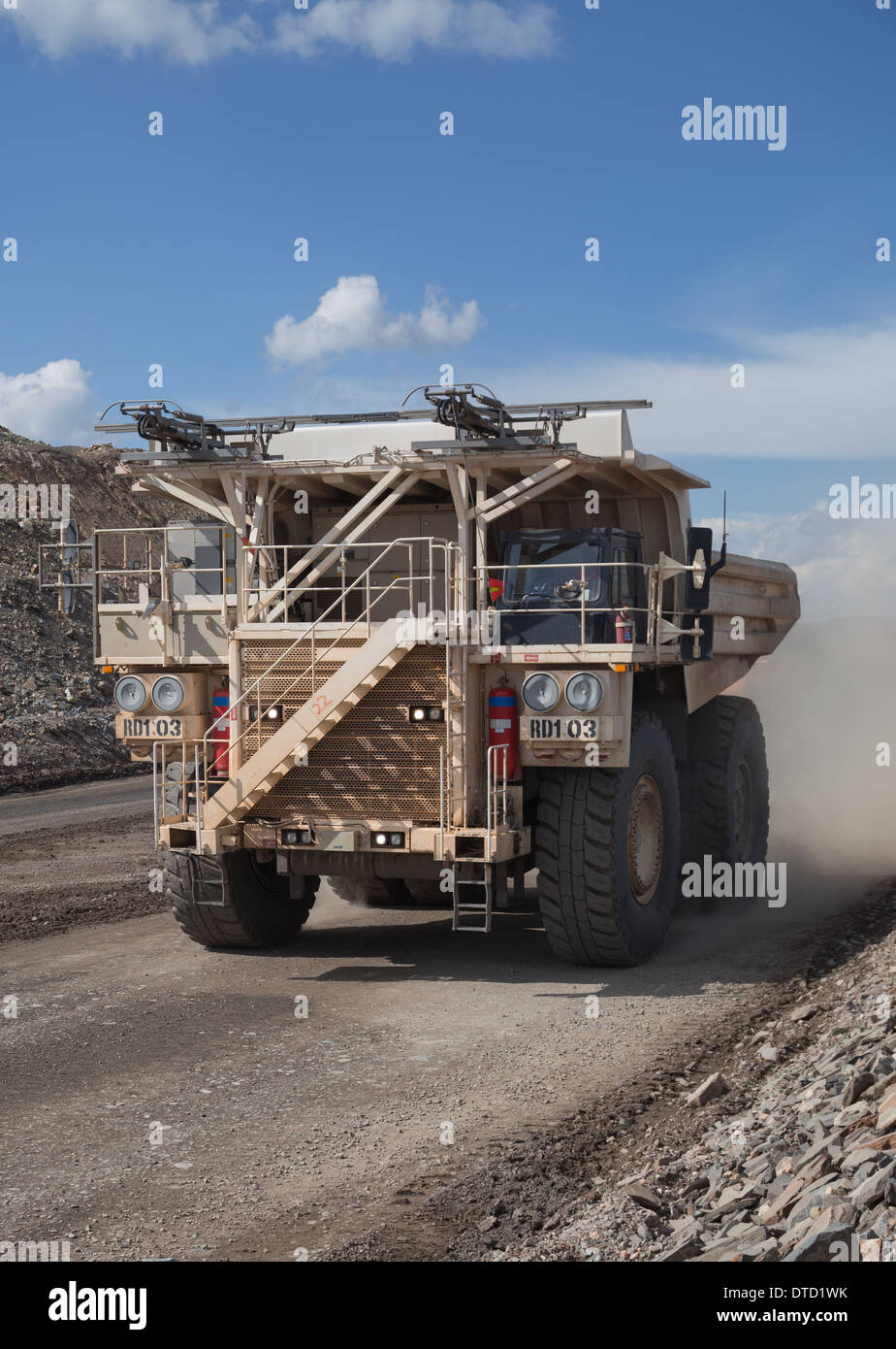 Massive white hitatchi dump truck driving in a large open cast copper and gold mine in Africa - Stock Image