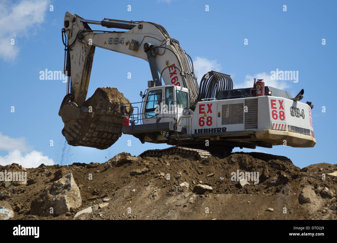 Excavator/ digger operator uses a Liebherr 984 to load oxide ore into the  back of a mining dump truck for delivery to the plant.