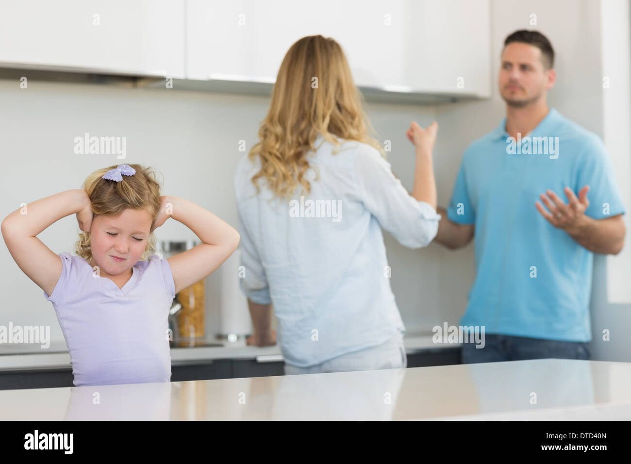 Girl covering ears while parents arguing - Stock Image