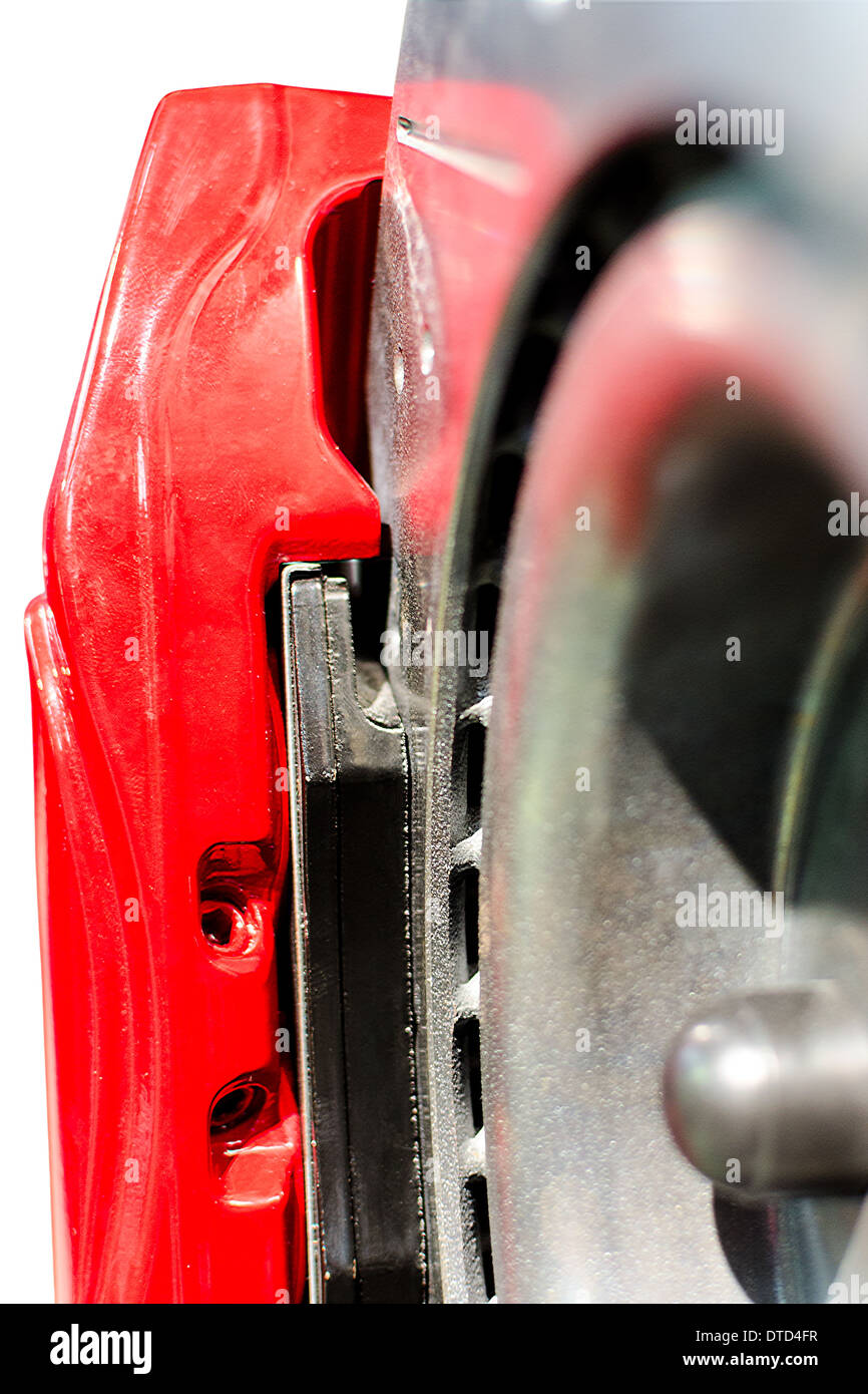 Closeup pads on disc car brake in red caliper isolated - Stock Image