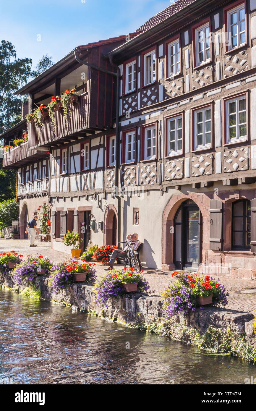 half-timbered house on the banks of a flower decked creek in the historic part of schiltach, black forest, baden-wuerttemberg - Stock Image