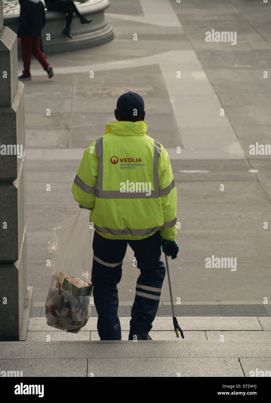 A council worker collecting litter in a bag with a pick up claw in Trafalgar Square, London - Stock Image