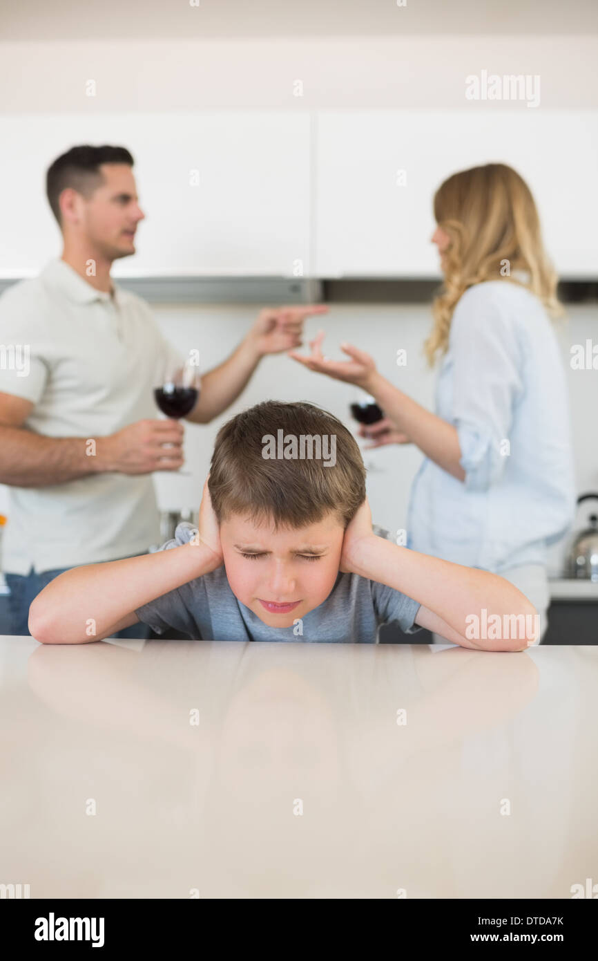 Irritated boy covering ears while parents arguing Stock Photo