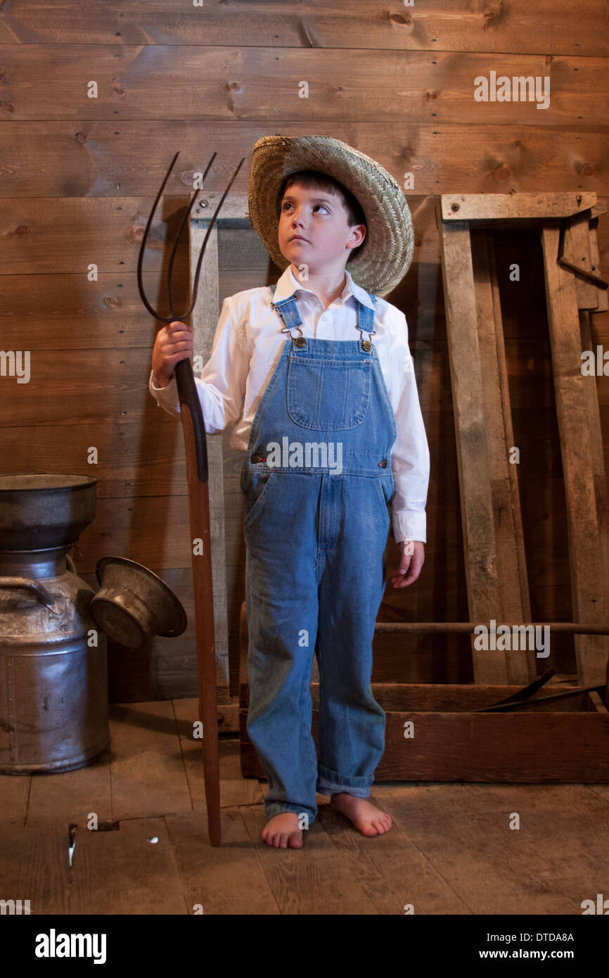 A young farmer boy holding a pitch fork - Stock Image