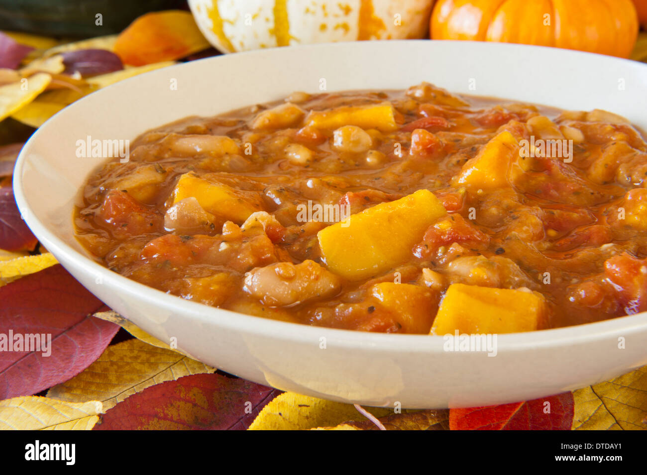 Hearty pumpkin stew with tomatoes, beans and vegetables - Stock Image