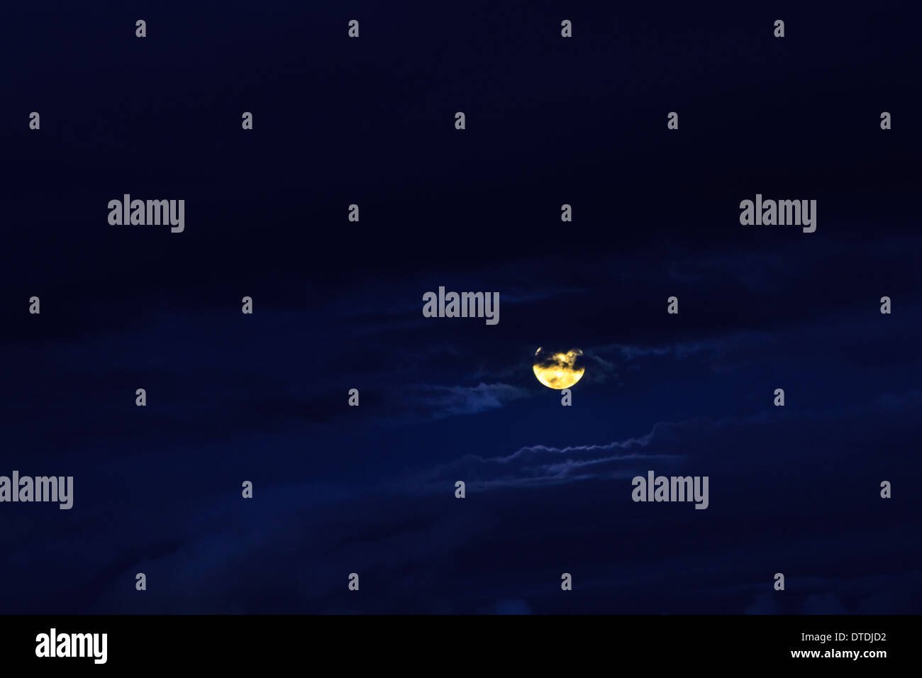Full yellow moon in a deep blue cloudy night sky - Stock Image