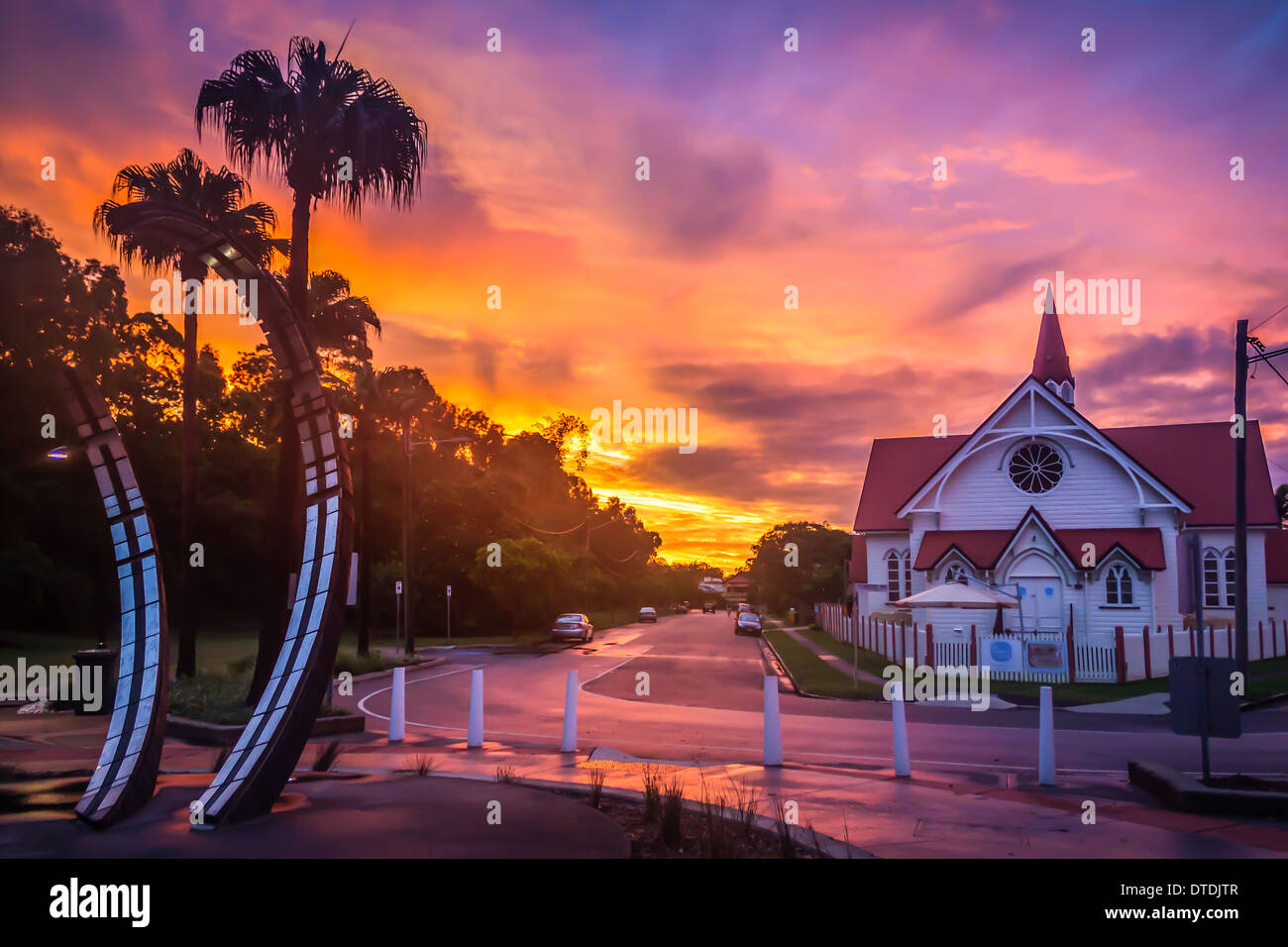 Dramatic sunset over Cliff St with the old Baptist Church at Sandgate in Brisbane. - Stock Image