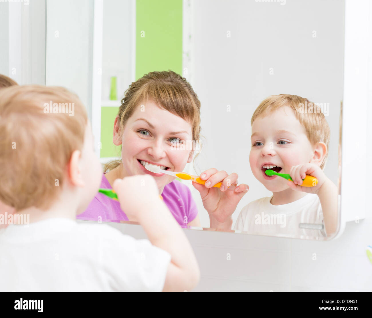 Happy mother and child teeth brushing in bathroom front of mirror - Stock Image