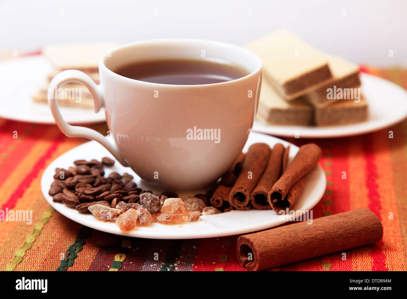 Cinnamon sticks with white cup on red background Stock Photo