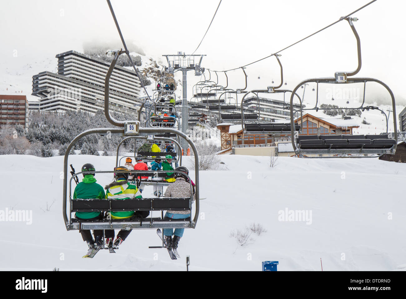 Skiers in a chairlift in Les Menuires, Trois Vallees, France Stock Photo