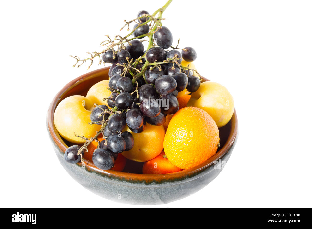 A bowl of fruit to include oranges and grapes - Stock Image