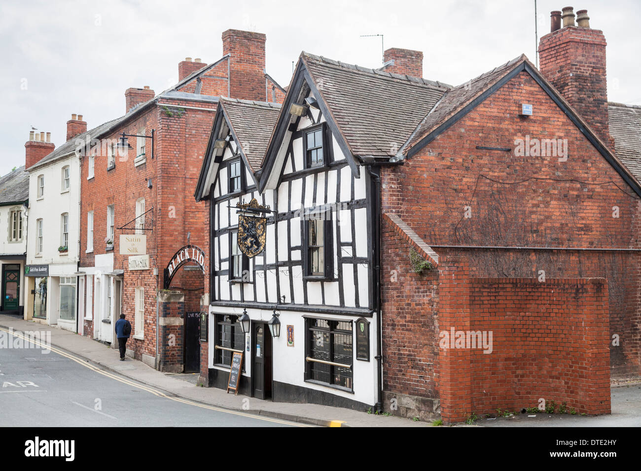 Man walks away from the Black Lion pub, a traditional historic black and white timbered building in Hereford, UK - Stock Image