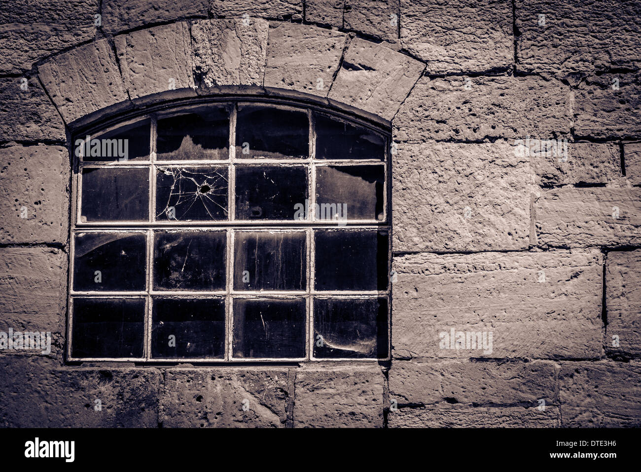 Ancient window in a stone cottage with a bullet hole in the glass - Stock Image