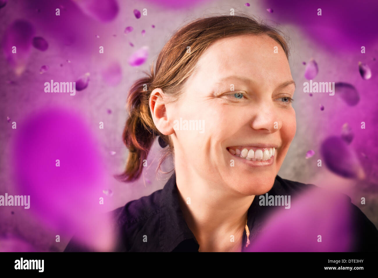 Smiling woman with flower petals falling. Spring season. - Stock Image