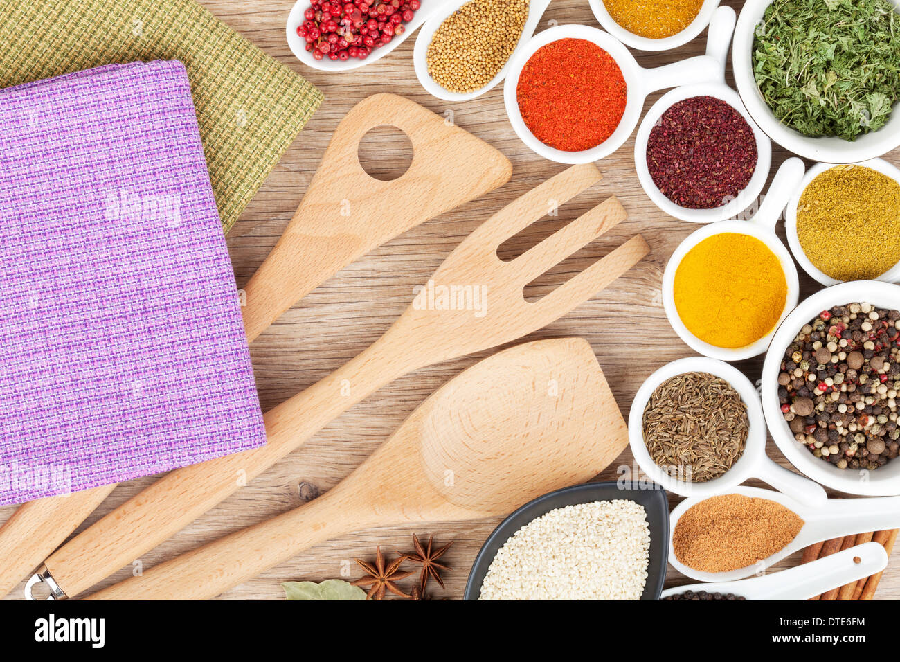 Various spices selection and kitchen utensils on wooden table - Stock Image