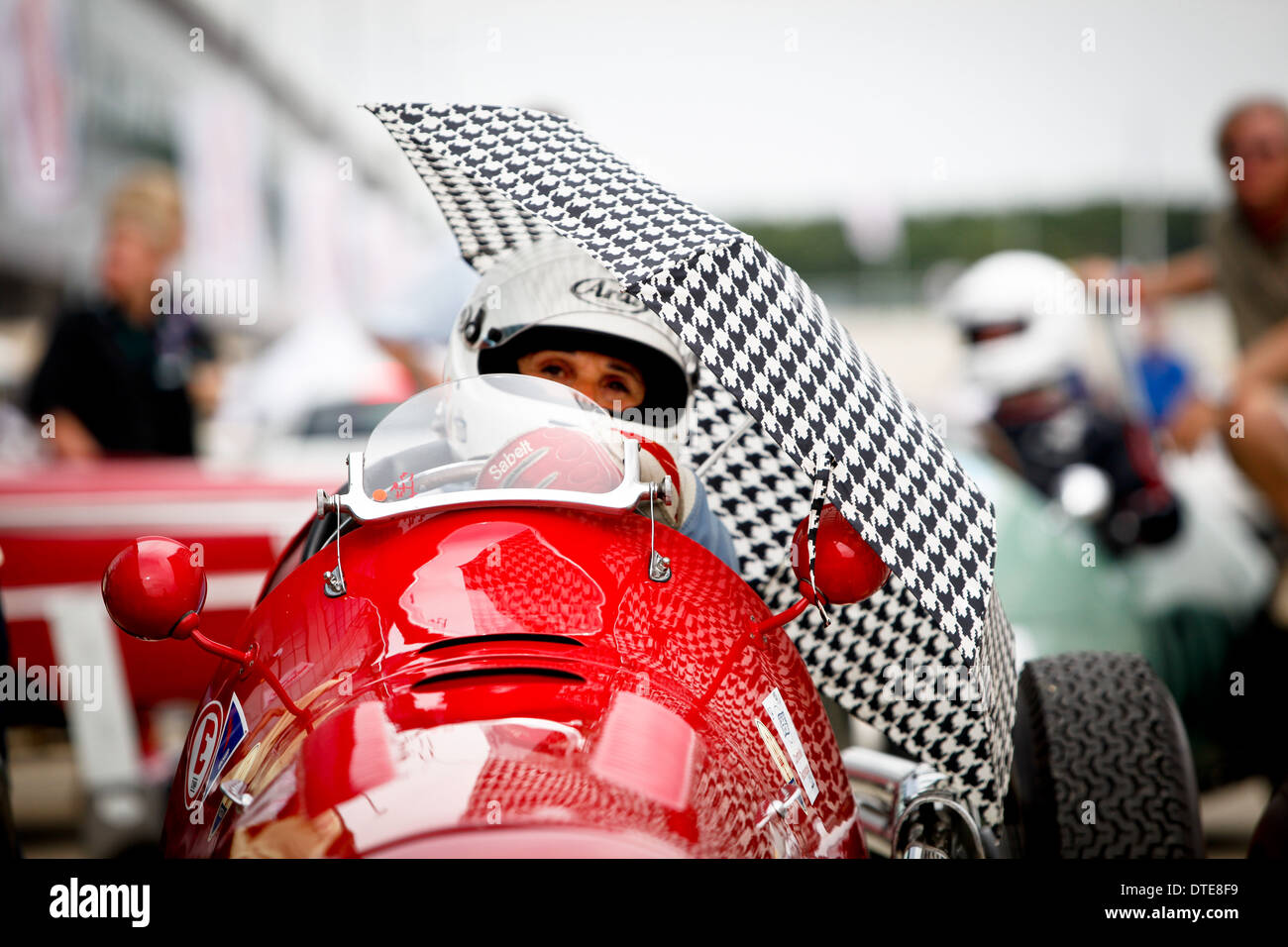 A female racing driver in a red single seater with a houndstooth check umbrella for shade - Stock Image
