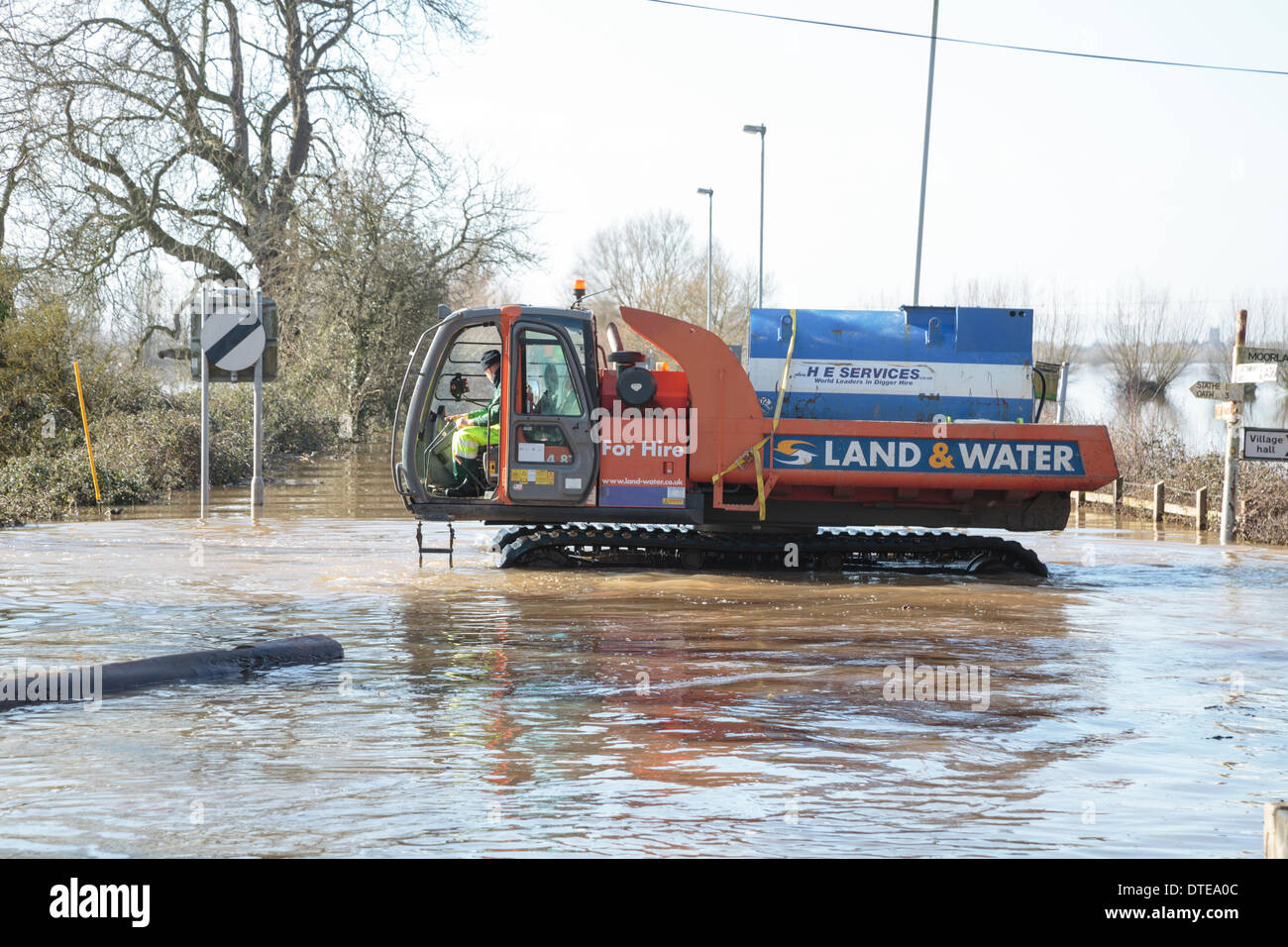 Burrowbridge, UK. 16th Feb, 2014. Workers make use of specialised vehicles during the heavy flooding at Burrowbridge on the Somerset Levels on February 16, 2014. Vehicles suitable for use in deep water are being used to remove obstacles such as tree trunks and telegraph poles from the water so that aid can be distributed to local residents. The A361 is a major arterial route across the Somerset Levels and has just experienced the worst flooding in living history and has been underwater now for seven weeks. Credit:  Nick Cable/Alamy Live News - Stock Image