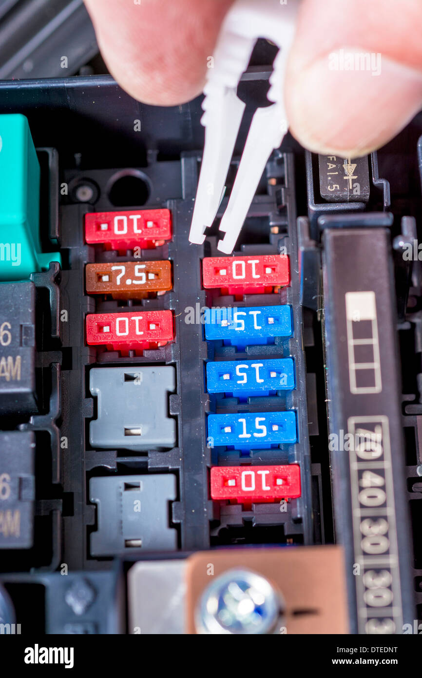 Pulling a fuSe out of a cars fuse box - Stock Image