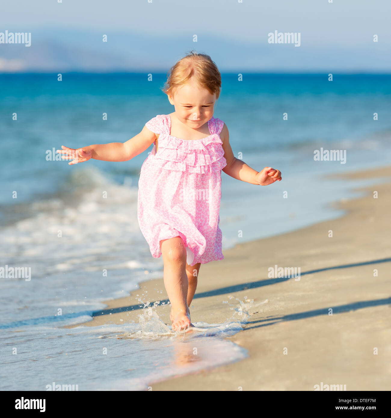 Little girl running on the beach Stock Photo