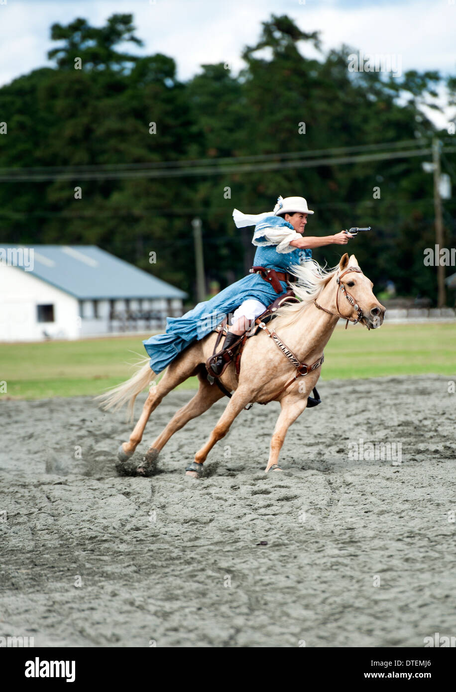 A cowgirl on a horse riding at full gallop with pistol drawn