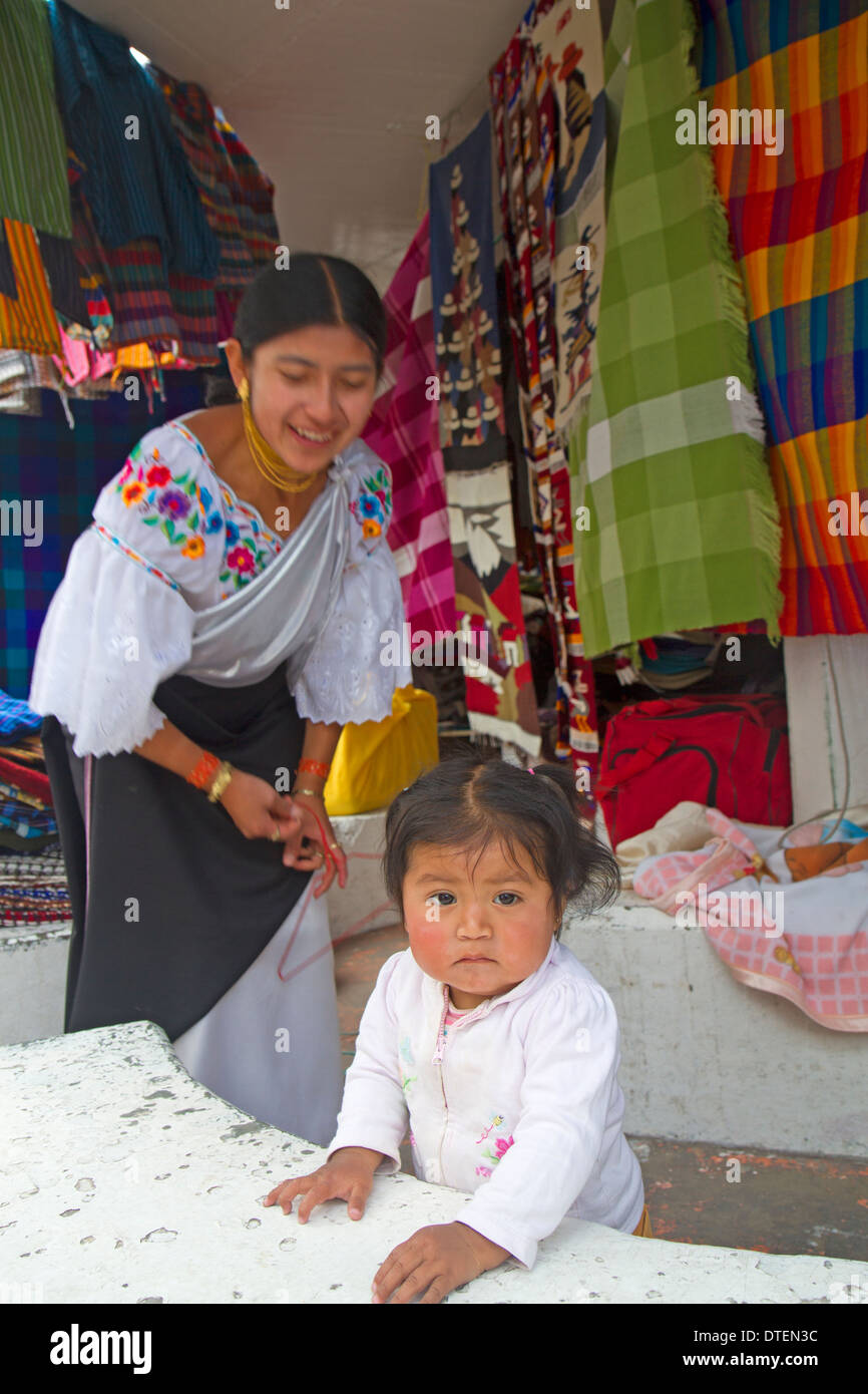 Baby girl and stallholder at the Otavalo market - Stock Image