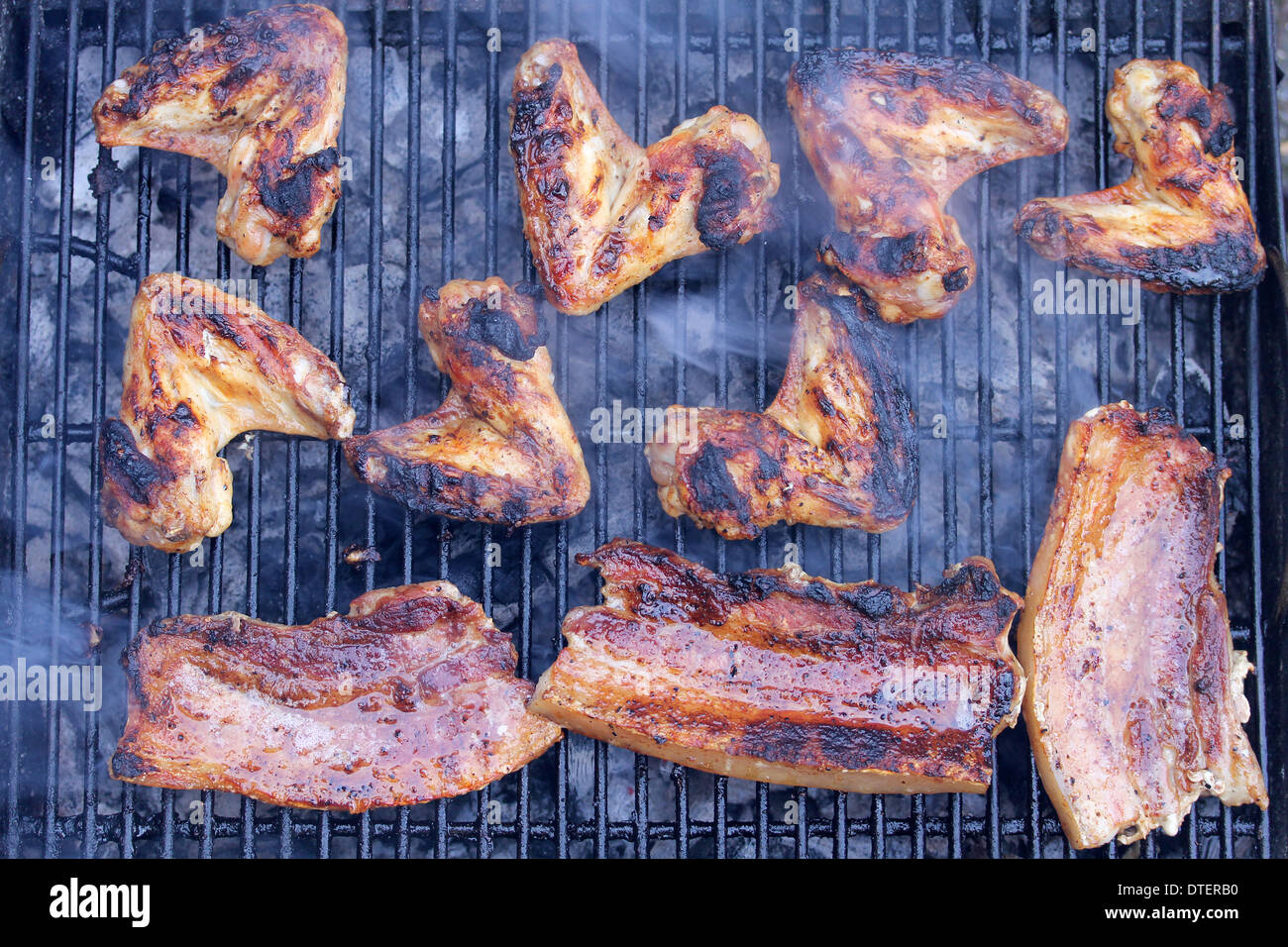 Chicken wings and bacon on the barbecue. - Stock Image