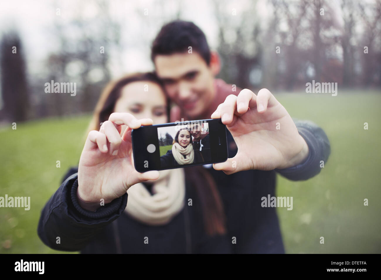 Cute young couple taking a self-portrait with a cell phone at the park. Mixed race teenage man and woman outdoors. - Stock Image
