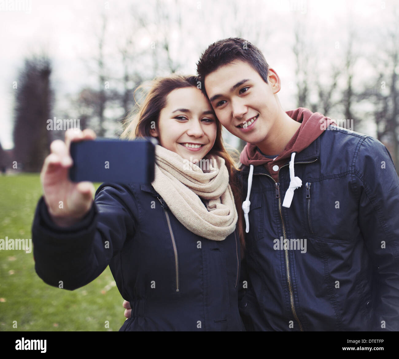 Cute young couple looking happy while taking pictures using a smart phone at the park. Mixed race teenage boy and - Stock Image