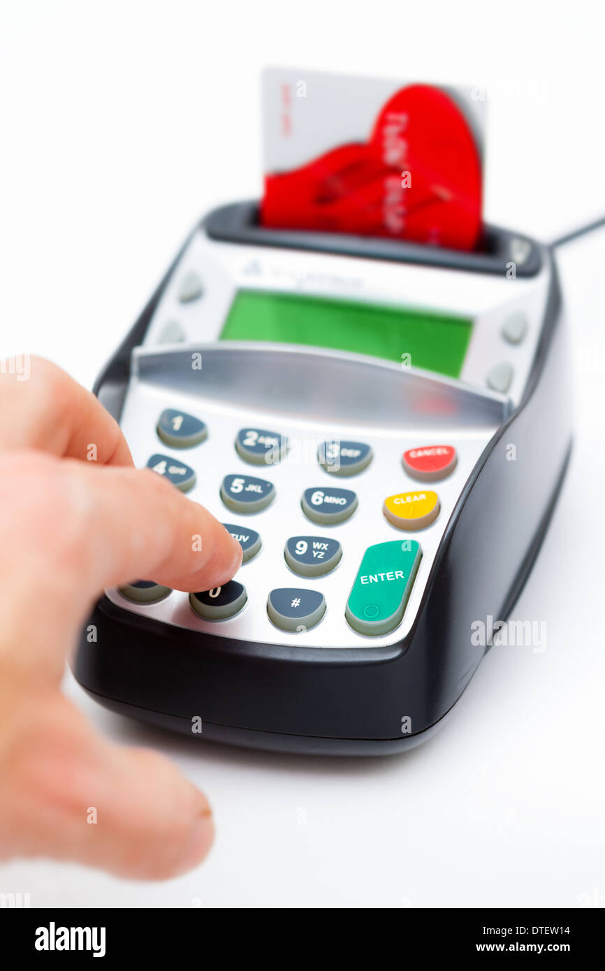 Close-up of a male hand entering number on a chip and PIN machine. Selective focus on the front of the machine. - Stock Image