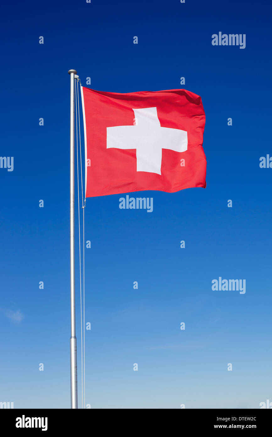 The national flag of Switzerland flying on a metal pole against a clear blue sky. - Stock Image